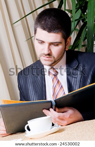 Man sitting on a restaurant and reading menu