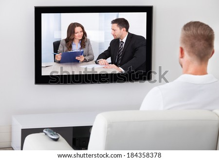 Man sitting on a sofa in his living room watching television alone at home - stock photo