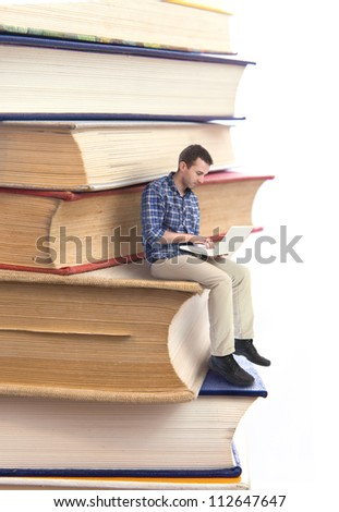 Man sitting on a stack of books and using laptop