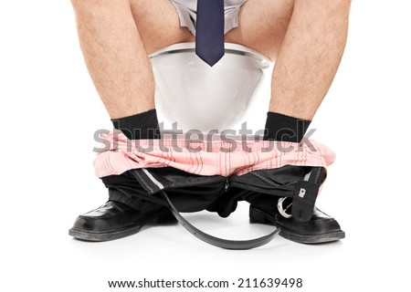 Man sitting on a toilet with his pants down isolated on white background - stock photo