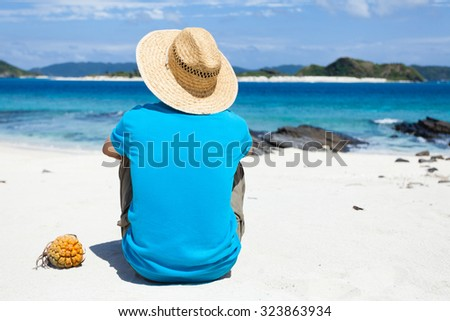 Man sitting on a tropical beach, looking at deserted coral islands on the horizon, Zamami Island of the Kerama Islands National Park, Okinawa, Japan - stock photo