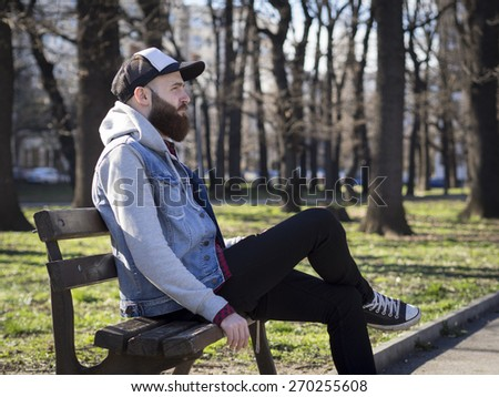 Man sitting on a wooden bench in the park with a baseball hat.  - stock photo