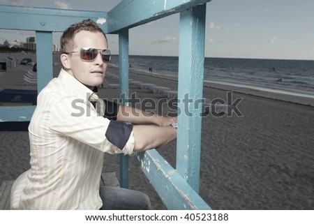 Man sitting on a wooden structure on the beach