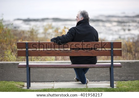 Man sitting on bench overlooking river.