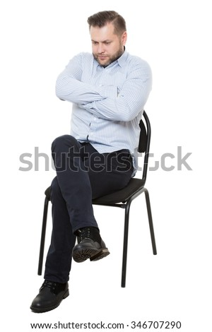 man sitting on chair. Isolated white background. Body language. gesture. Training managers. sales agents.  fully closed position. lowered eyes, drawn-neck, arms and legs crossed - stock photo
