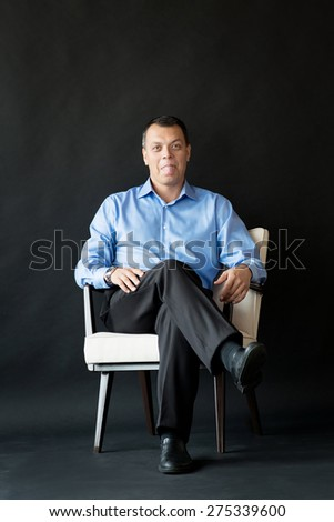 Man sitting on chair. Mouth, tongue - stock photo