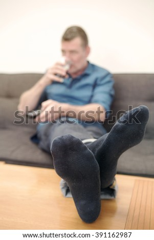 man sitting on couch, drinking beer and watching tv