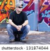 Man sitting on crate with graffiti background - stock photo