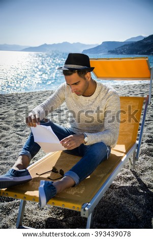 Man sitting on deckchair while reading letter