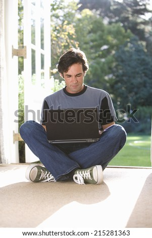 Man sitting on floor by French doors, legs crossed, laptop on lap