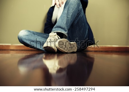 Man sitting on floor leaning on the wall. Very shallow depth of field, edited with vintage colors - stock photo