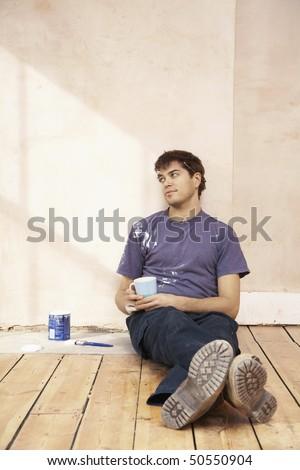 Man sitting on floor of unrenovated room, holding coffee mug - stock photo