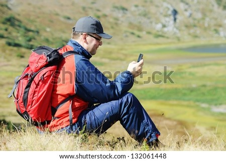 Man sitting on mountain and searching for mobile signal - stock photo