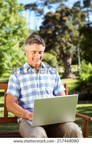 Man sitting on park bench using laptop on a sunny day