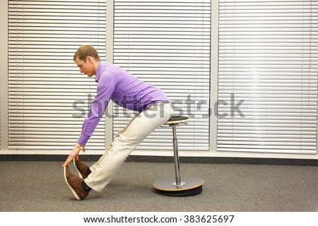 man sitting on pneumatic stool exercising touching his toes in office