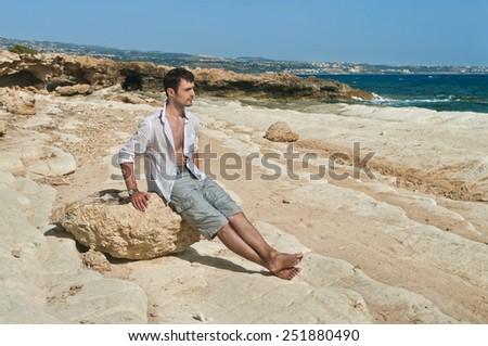 man sitting on rock at sea near Coral Bay, cyprus - stock photo