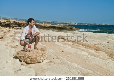 man sitting on rock looking at sea near coral bay, cyprus - stock photo