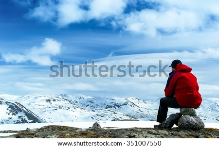 Man sitting on rocks and looking at the snow-covered hills. Blue sky with clouds. Norway - stock photo