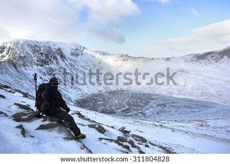 man sitting on side of ice and snow covered mountain looking at the view, helvellyn, lake district - stock photo