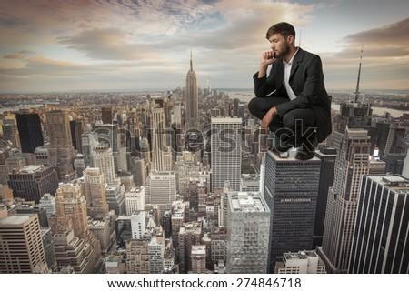 Man sitting on Skyscraper, Studio Shot, Montage - stock photo