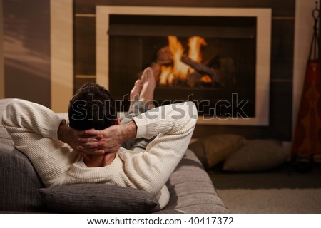 Man sitting on sofa at home in front of fireplace, rear view.