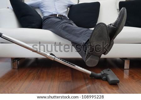 man sitting on sofa, feet up to vacuuming - stock photo