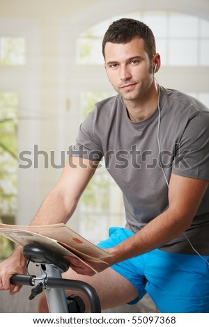 Man sitting on stationary bike at home, reading newspaper and listening music.