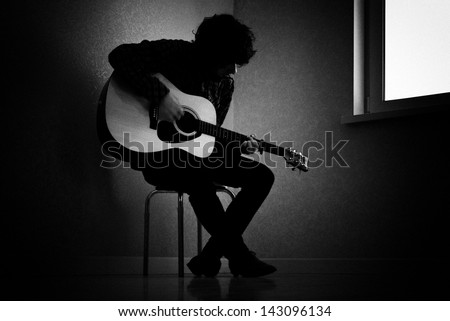 Man sitting on stool in dark room playing guitar - stock photo