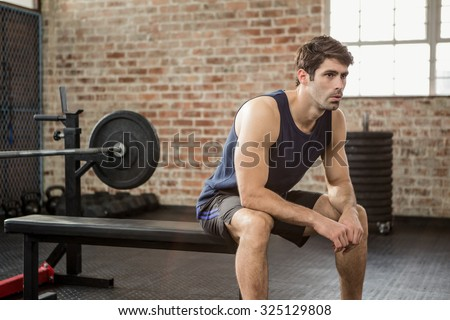 Man sitting on the bench at gym - stock photo