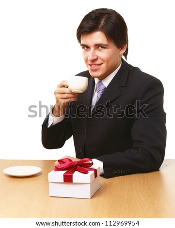 Man sitting on the desk with cup of coffee, gift on the desk - stock photo