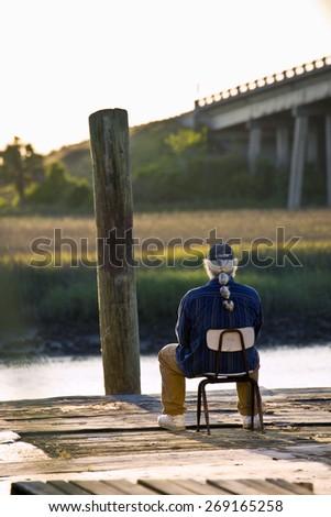 Man sitting on the dock overlooking Lazaretto Creek on Tybee Island, Georgia, USA. - stock photo