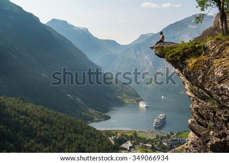 Man sitting on the edge of a cliff and looking at Geiranger Fjord, Norway - stock photo