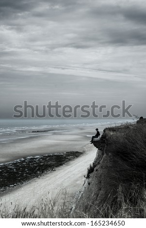 Man sitting on the edge of cliff waiting the sea - stock photo