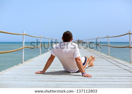 Man sitting  on the pier of Red Sea, Egypt