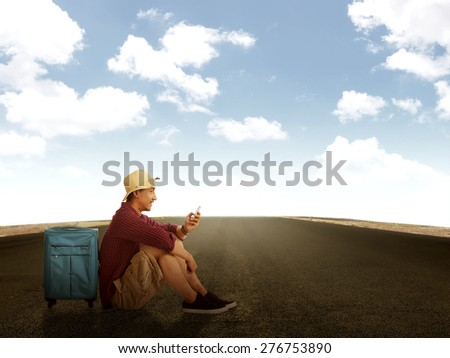 Man sitting on the road, playing with cellphone. Travel concept - stock photo