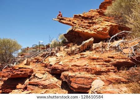 Man sitting on the rock edge, Loop walk, Kalbarri national park, Western Australia - stock photo