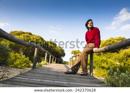 Man sitting on the rustic wooden railings of a coastal boardwalk crossing the dunes and beach sand, as he relaxes and enjoys the sunshine and the tranquility of nature. - stock photo