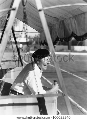 Man sitting on the sideline of a tennis court enjoying a game - stock photo