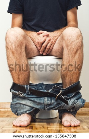 Man sitting on toilet with his pants down. - stock photo