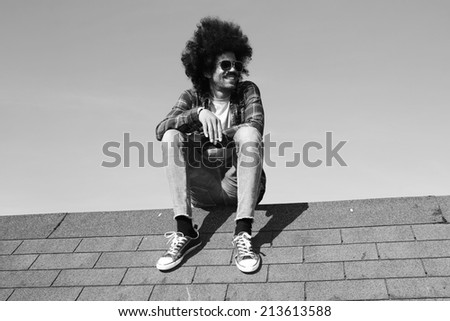 Man sitting on top of the roof - stock photo