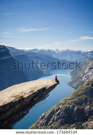 man sitting on trolltunga rock in norway  - stock photo