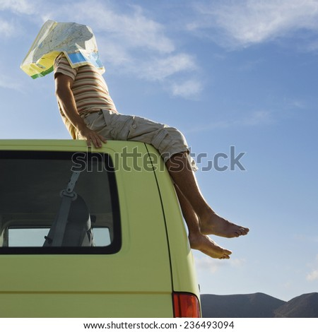 Man Sitting on Van Roof with Map