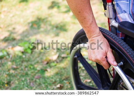 Man sitting on wheelchair, Close up hand on wheel
