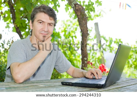 man sitting outdoor working with a laptop - stock photo
