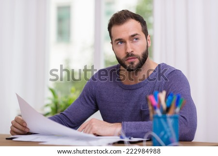 Man sitting thinking at his desk holding a sheet of paper in his hand and looking pensively off to the side - stock photo