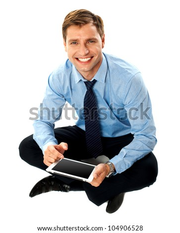 Man sitting with crossed legs using touch screen device isolated against white background