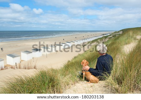 Man sitting with dog in the dunes and looking to the huts - stock photo