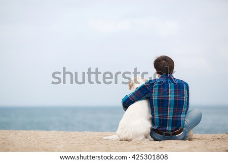 Man sitting with dog on sand dune. man with his dog at the summer beach sitting back to camera - stock photo