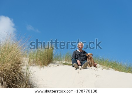 Man sitting with dog on top of the dunes - stock photo