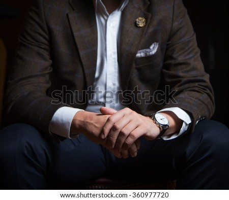 Man sitting with his hands crossed - stock photo